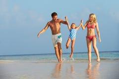Familj som har gyckel i havet på strandferie Royaltyfri Bild