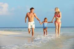 Familj som har gyckel i havet på strandferie Fotografering för Bildbyråer