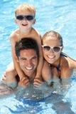 Familj som har gyckel i simbassäng Arkivfoton
