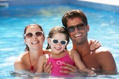 Familj som har gyckel i simbassäng Arkivbild