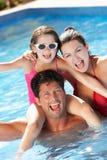 Familj som har gyckel i simbassäng Royaltyfri Fotografi