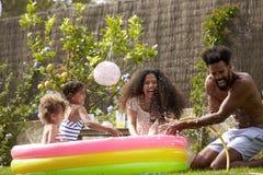 Familj som har gyckel i trädgårds- paddla pöl royaltyfria foton