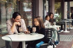 Familj som har gyckel i utomhus- kafé Fotografering för Bildbyråer