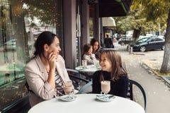 Familj som har gyckel i utomhus- kafé Royaltyfri Bild