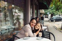 Familj som har gyckel i utomhus- kafé Arkivbild