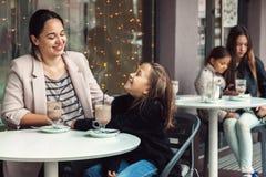 Familj som har gyckel i utomhus- kafé Royaltyfria Bilder