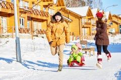 Familj som har gyckel i vinter royaltyfria bilder