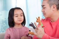 Familj som har gyckel med handdockor Fotografering för Bildbyråer