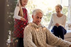 Familj som har gyckel, medan dekorera huset under jul arkivfoto