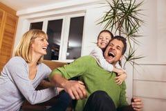 Familj som har gyckel på golvet av i vardagsrum hemma som skrattar royaltyfri fotografi