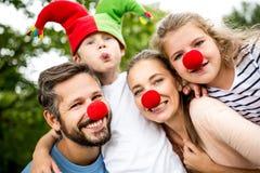Familj som har gyckel på karnevalet arkivbilder