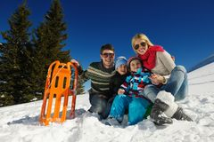 Familj som har gyckel på ny snö på vintern Arkivbild