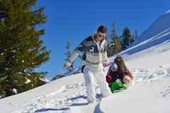 Familj som har gyckel på ny snö på vintersemestern Royaltyfri Bild