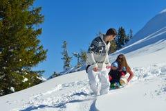 Familj som har gyckel på ny snö på vintersemestern Arkivbild