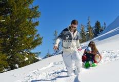Familj som har gyckel på ny snö på vintersemestern Royaltyfri Fotografi