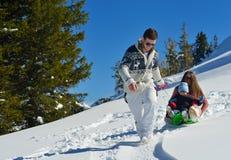 Familj som har gyckel på ny snö på vintersemestern Arkivbilder