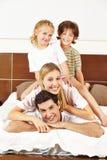 Familj som har gyckel på säng Royaltyfria Foton