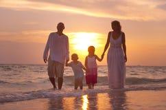 Familj som har gyckel på semester med perfekt solnedgång Royaltyfri Bild
