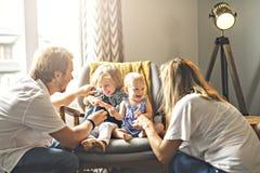 Familj som har gyckel på stol royaltyfri fotografi
