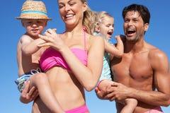 Familj som har gyckel på strand Arkivbild