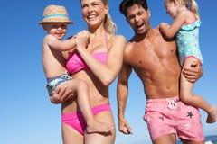 Familj som har gyckel på strand Arkivfoto