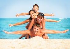 Familj som har gyckel på stranden Arkivbild
