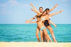 Familj som har gyckel på stranden fotografering för bildbyråer