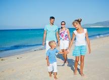 Familj som har gyckel på stranden Arkivbilder