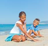 Familj som har gyckel på stranden Royaltyfria Bilder