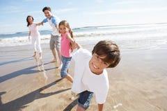 Familj som har gyckel på strandferie Arkivfoton