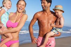 Familj som har gyckel på strand Royaltyfri Bild