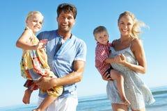 Familj som har gyckel på strand Royaltyfria Foton