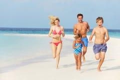 Familj som har gyckel på strandferie Arkivfoto