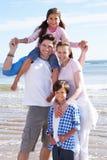Familj som har gyckel på strandferie Royaltyfri Foto