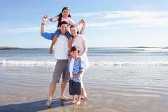 Familj som har gyckel på strandferie Royaltyfri Fotografi