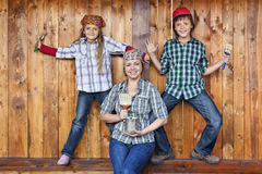Familj som har gyckel som målar träskjulet om igen Arkivbilder