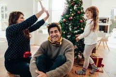 Familj som har gyckel tillsammans på jul royaltyfri bild