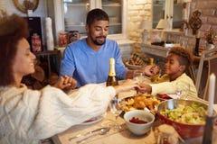 Familj som har julbönen för matställe hemma royaltyfri foto