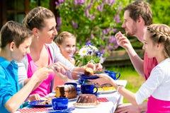 Familj som har kaffetid i trädgårds- ätakaka Royaltyfria Foton
