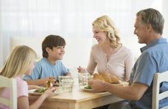 Familj som har mål på att äta middag tabellen royaltyfria bilder