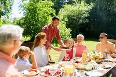 Familj som har matställen eller grillfesten på sommarträdgården arkivbild