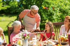 Familj som har matställen eller grillfesten på sommarträdgården royaltyfria bilder