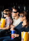 Familj som har mellanmål, medan hålla ögonen på filmen 3D Arkivfoton