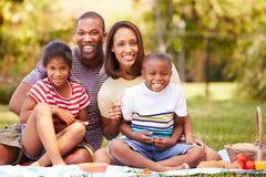 Familj som har picknicken i trädgård tillsammans Royaltyfria Foton