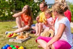Familj som har picknicken i trädgårdframdel av deras hem Royaltyfria Foton