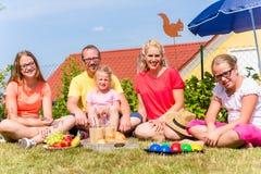 Familj som har picknicken i trädgårdframdel av deras hem Arkivfoton