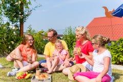 Familj som har picknicken i trädgårdframdel av deras hem Arkivbilder