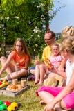 Familj som har picknicken i trädgårdframdel av deras hem Royaltyfri Fotografi