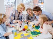 Familj som har roliga måla och dekorera easter ägg arkivfoton