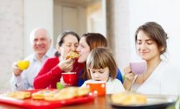 Familj som har tea med tårtor royaltyfria foton